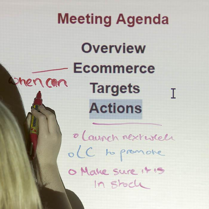 Woman writing and projecting on Smart Self Adhesive Whiteboard Film Low Sheen