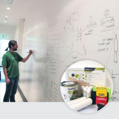 man using a smart whiteboard paint white wall with kit contents on display