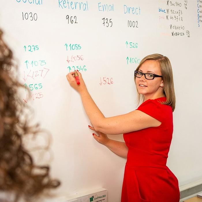 Smarter Surfaces Woman using Smart Whiteboard Paint coated wall to write monthly figures
