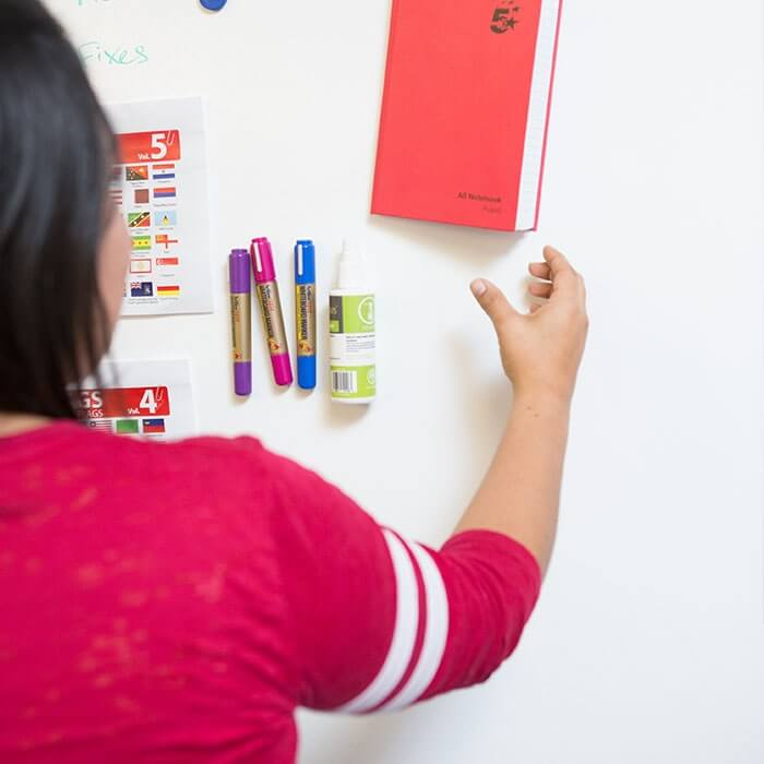 Woman hanging up notebook on Magnetic wall