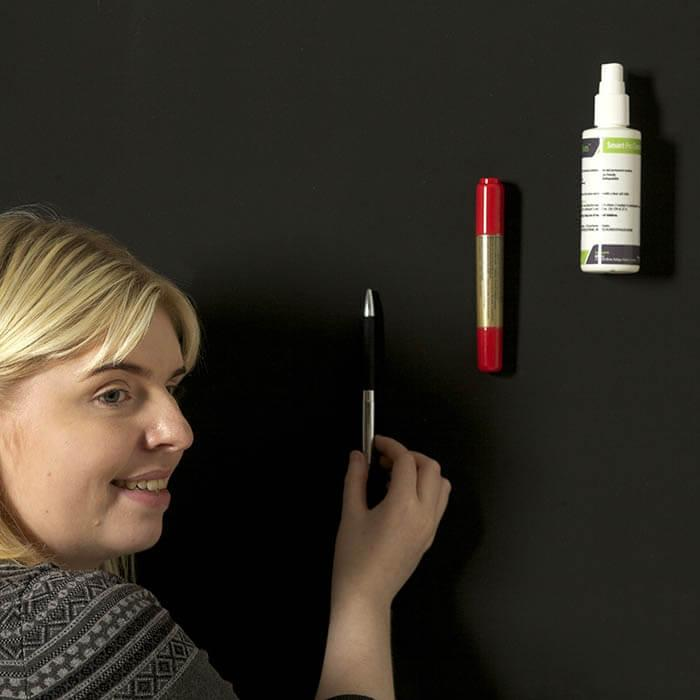 woman sticking up items on Super Magnetic Paint