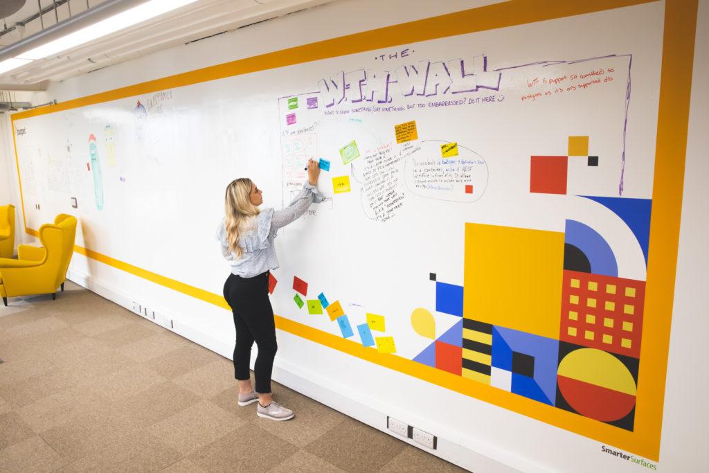 woman-writing-on-whiteboard-wall